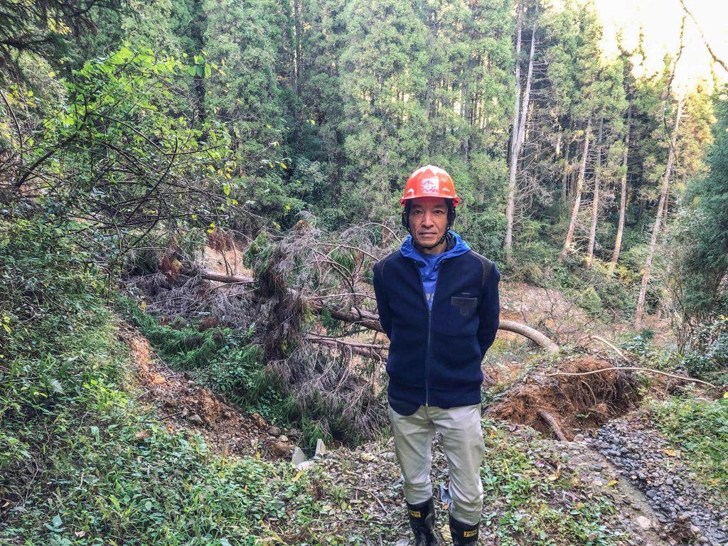 大分県日田市の被災した山林を背景に編集長樫村